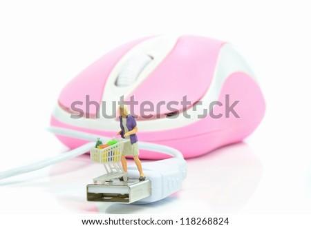 Mini female customer with shopping cart on mouse usb plug. Internet shopping concept - stock photo