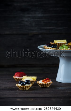 Mini fresh fruit tartlets on platter with wooden background - stock photo