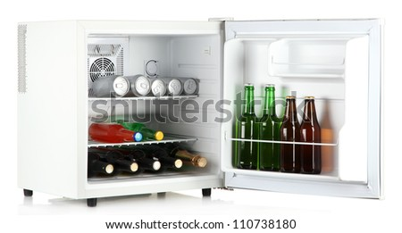 Mini fridge full of bottles of alcoholic beverages isolated on white - stock photo