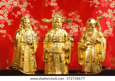 Mini Golden Sculpture of Three gods of the Chinese, Fu Lu Shou. (Hock Lok Siew),  The Gods of Good Fortune, Prosperity, and Longevity for decoration, Chinese Gods. Isolated on Red (Chinese Belief)