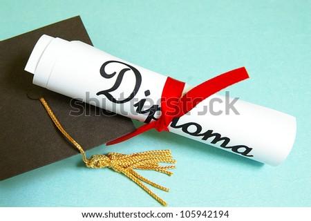 mini graduation cap and diploma - stock photo