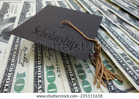 Mini graduation mortar board with Scholarship text, on money