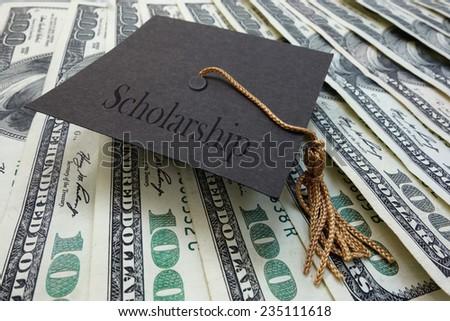 Mini graduation mortar board with Scholarship text, on money                                - stock photo