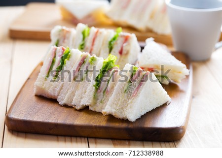 mini ham sandwich with dressing and vegetable on wooden board