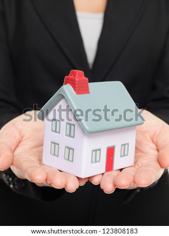 Mini house. New house concept with realtor real estate agent showing miniature house.