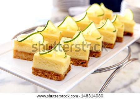 Mini lemon cheese cake on white disc - stock photo