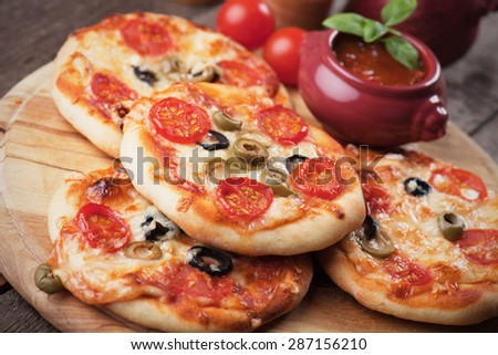 Mini margherita pizzas with cheese, olive and tomato - stock photo