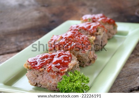 Mini Meat loaf's on a tray with parsley. - stock photo