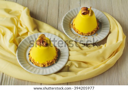 Mini mousse cakes with banana covered with yellow glaze. Modern european cake on light wooden background