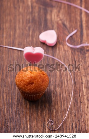 Mini muffin with a candle in the shape of a heart. - stock photo