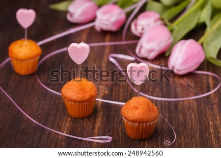 Mini muffin with a candle in the shape of a heart and pink tulips. - stock photo
