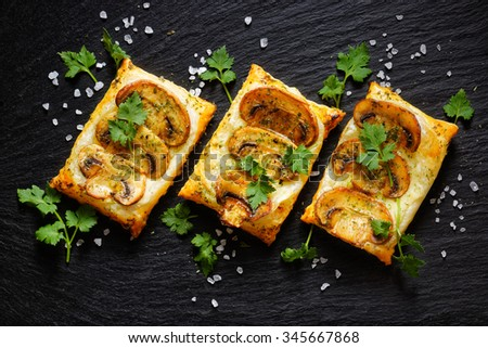 Mini mushroom tarts with puff pastry . Delicious vegetarian appetizer - stock photo