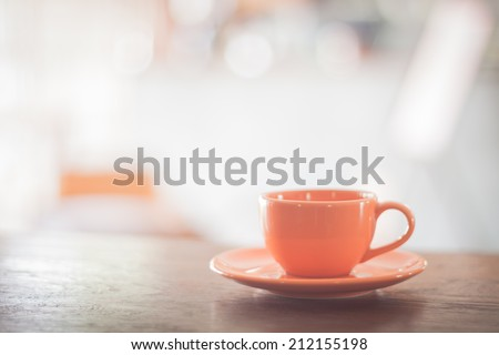 Mini orange coffee cup on wooden table - stock photo