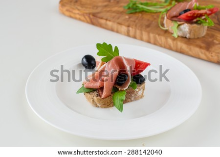 Mini party sandwich with ham, rocket, olives on the white plate.