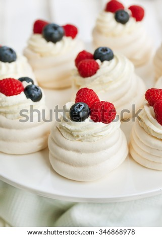Mini Pavlova meringue cakes decorated with fresh berries - stock photo
