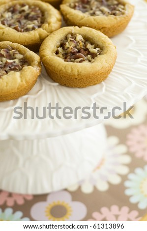 Mini Pecan Pie Tarts on a Flowery White Cakeplate - stock photo