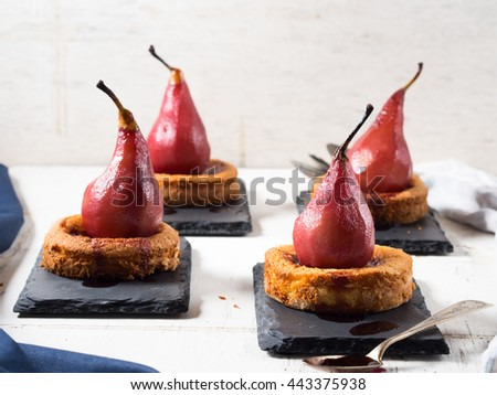 Mini polenta pies with pears in red wine sauce on black slate plates on white rustic wooden background  - stock photo