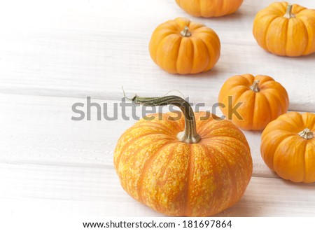 Mini Pumpkins scattered on Rough White Painted Boards as Background with room or space for copy, text or words.  Horizontal - stock photo