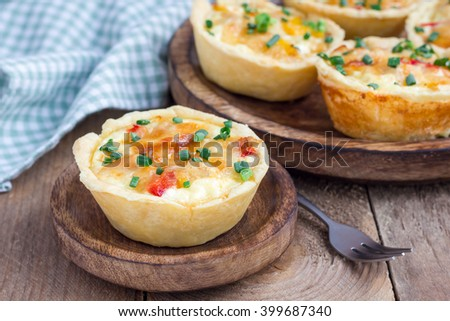 Mini quiche with chicken and bell pepper on a wooden plate - stock photo