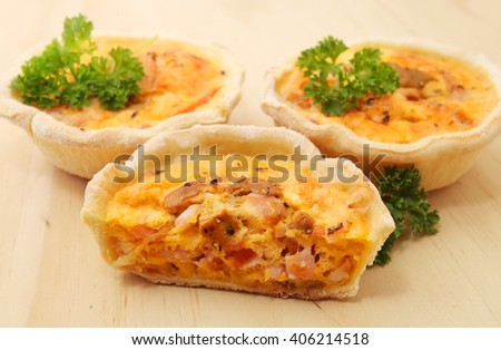 Mini Quiches over wooden table background - stock photo