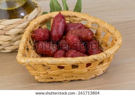Mini salami sausage on the wood background - stock photo