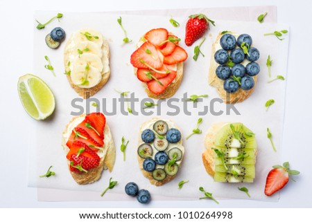 Mini sandwiches with cream cheese, fruits and berries. Sandwiches with cheese, strawberries, blueberries, bananas, kiwi and lemon zest on a light background, top view. Flat lay