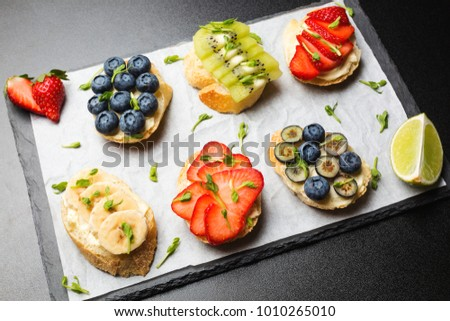 Mini-sandwiches with cream cheese, fruits and berries. Sandwiches with cheese, strawberries, blueberries, bananas, kiwi and lemon zest on a dark background, top view.