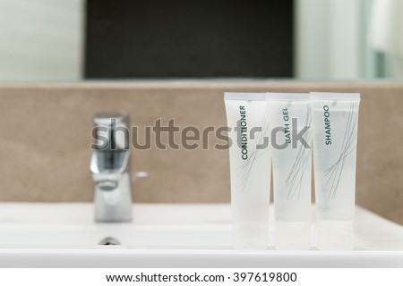 Mini set of bath gel, shampoo and hair conditioner in bathroom - stock photo