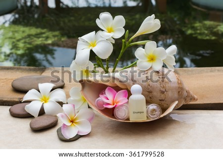 Mini set of bubble bath and shower gel beside the pool decorated with fragrant beautiful flower  - stock photo