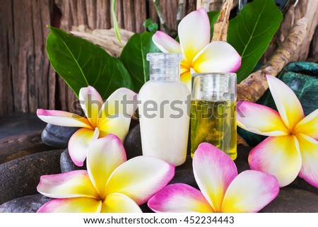 Mini set of bubble bath and shower gel liquid with pink flower on stone and wood background, shampoo conditioner treatment spa shower