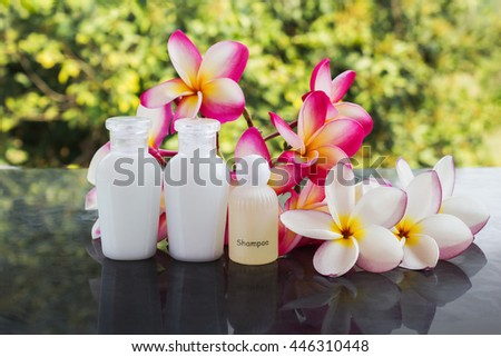 Mini set of bubble bath and shower gel liquid with pink flower on tree bush background group of spa body and hair treatment on green nature relaxing feeling background - stock photo