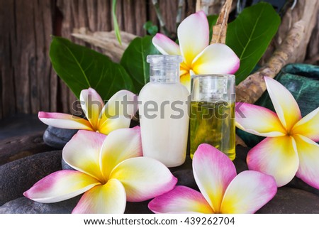 Mini set of bubble bath and shower gel liquid with pink white and yellow flowers plumeria or frangiani on pebble rock with green leaf and timber or wooden background with relax and spa mood