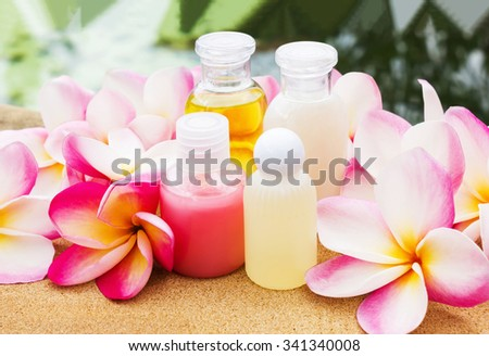 Mini set of bubble bath and shower gel on rock tile floor beside the pool decorated with fragrant beautiful flowers with sweet feeling - stock photo