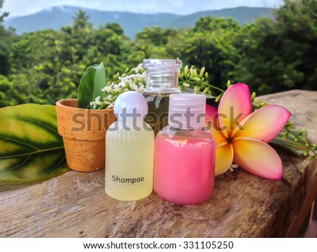 Mini set of bubble bath and shower gel put on wood  shelf decorated with lovely flowers on fresh green nature view background - stock photo