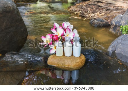 Mini set of bubble bath shower gel liquid spa with flowers and pebble on waterfall rock  with natural water relaxing feeling background and copy space - stock photo