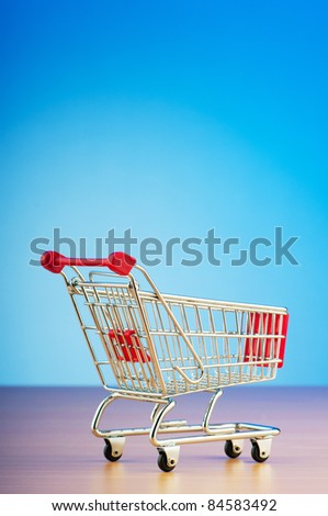 Mini shopping cart against gradient background - stock photo