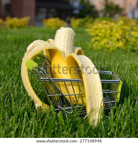 mini shopping cart with banana outdoor in green grass - stock photo