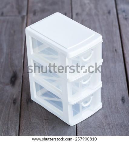 mini storage plastic box for office on wood background - stock photo