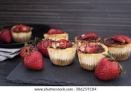 Mini strawberry cheesecake in muffin forms. Served in black stone plateau with fresh strawberries. Black wood background. - stock photo