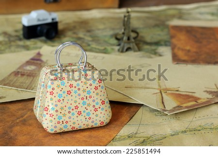 Mini suitcase and travel objects in a vintage background. Travel concept. - stock photo