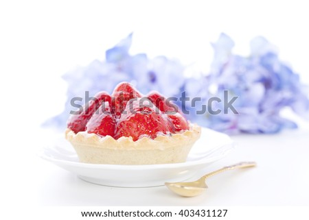 Mini tart with fresh strawberries on plate on a white background.