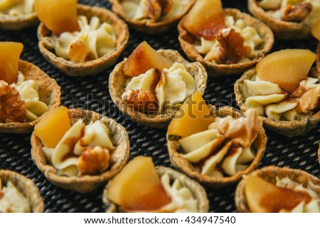 Mini tartlet appetizers with apple and walnut all lined up ready to be eaten. - stock photo