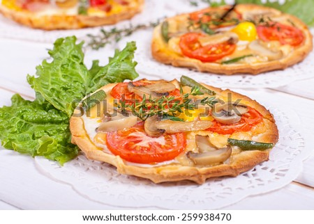 Mini tartlets with champignon, tomato, cheese, quail eggs and black eyed peas on white wooden background - stock photo