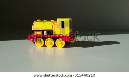 Mini train toy. Plastic train model. Photo with shades
