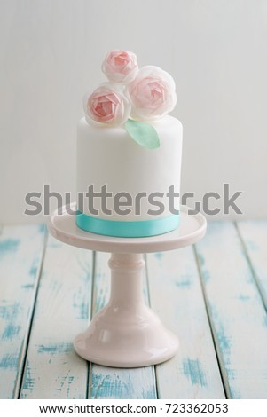 Mini White Fondant Covered Wedding Cake With Wafer Paper Ranunculus Flowers On Pink Stand