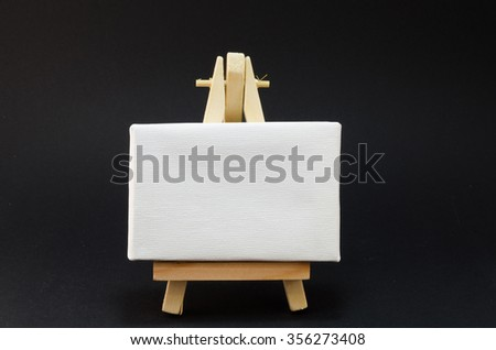 Miniature artist easel, isolated on black background.