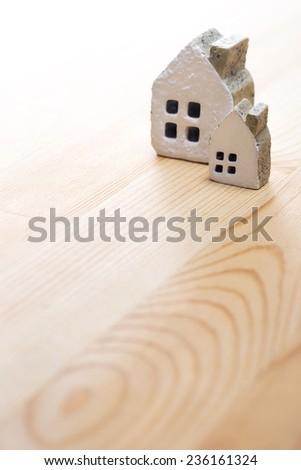 Miniature brick house on wooden floor - stock photo