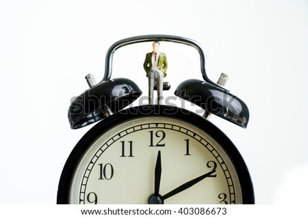 Miniature businessman stand on the clock time management concept