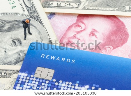 miniature businessman standing on the banknote with credit card - stock photo