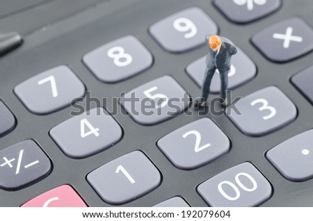 miniature businessman standing on the calculator - stock photo
